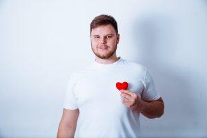 Big,Man,Holds,Little,Plush,Heart,On,White,Bakground